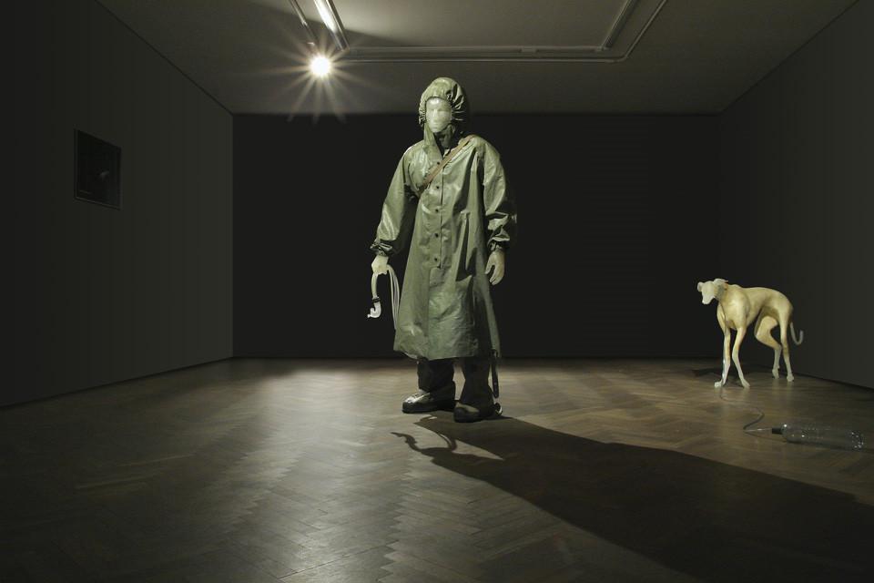 Na zdjęciu rzeźba chłopca i psa w zaciemnionej sali wystawowej