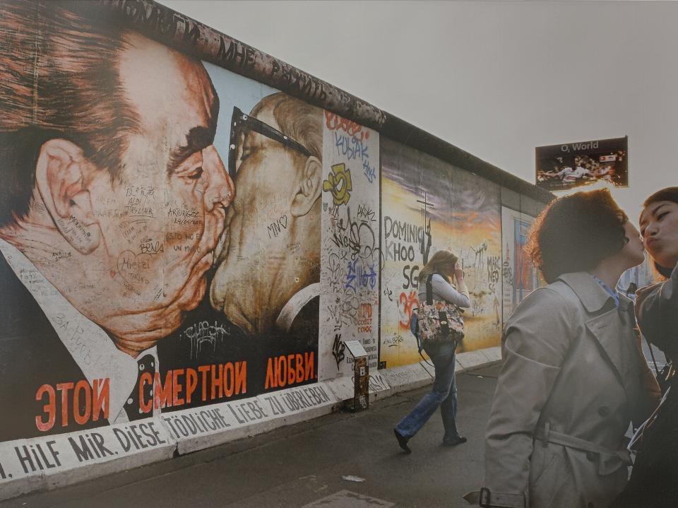 Zdjęcie przedstawia dwie młode kobiety na tle muru berlińskiego pokrytego graffiti.