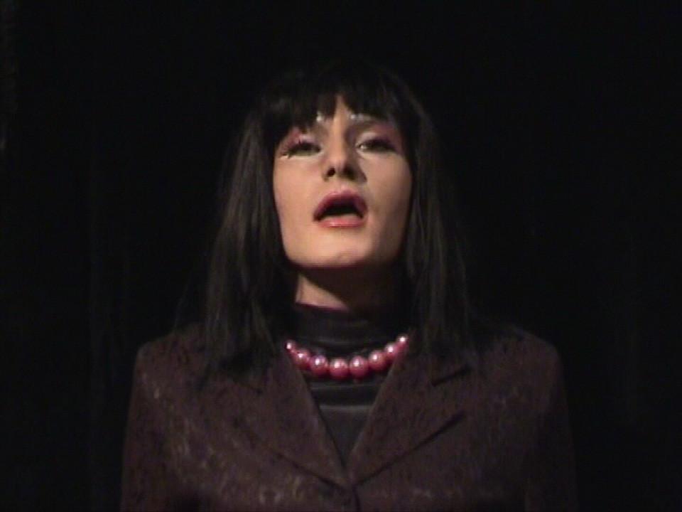 Kadr z filmu. Przedstawia głowę oraz klatkę piersiową elegancko ubranego transwestyty. Tło pomieszczenia, w którym znajduje się mężczyzna, jest czarne.
