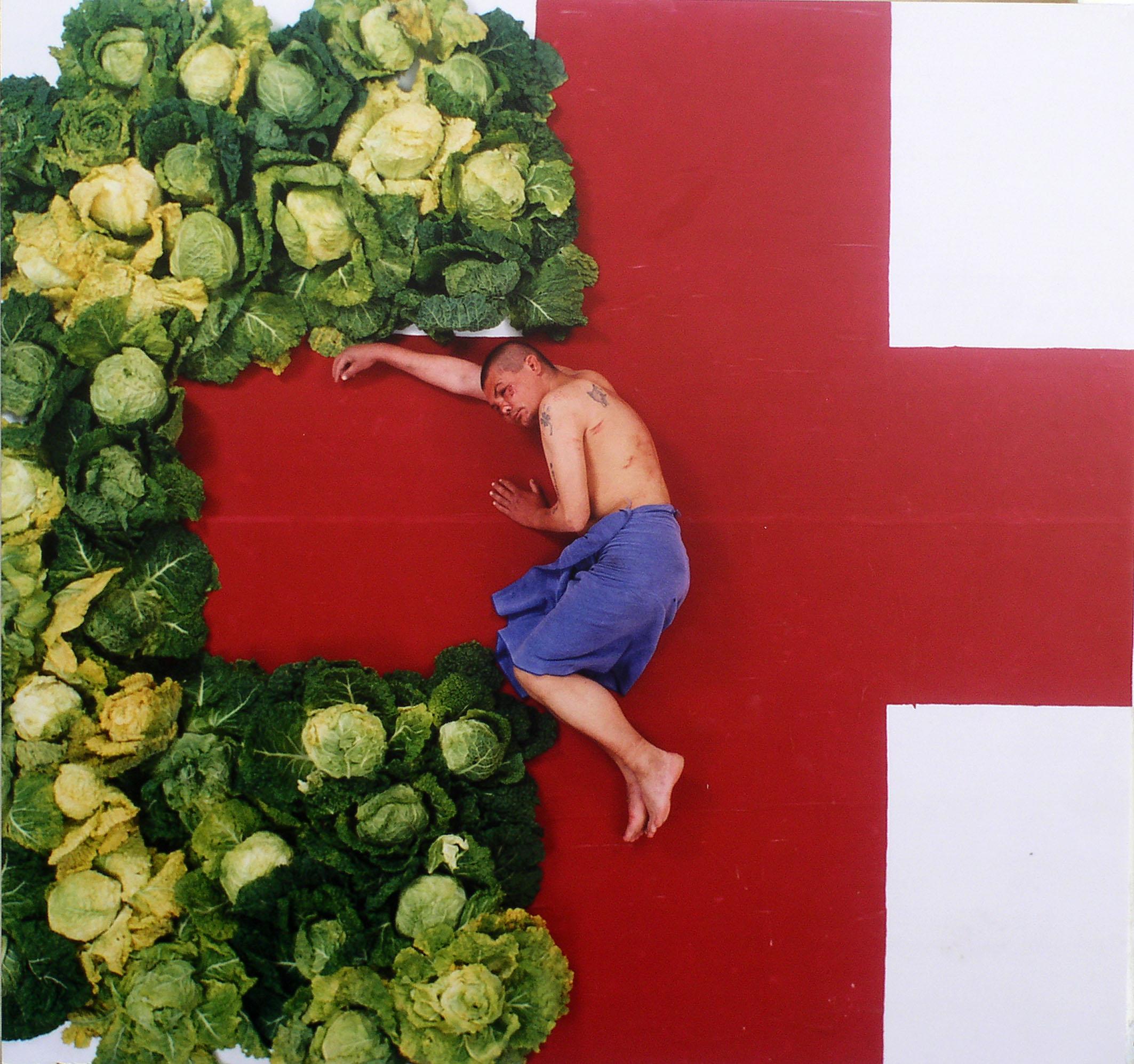 Pół nagi mężczyzna, leżący na tle czerwonego krzyża i otoczonego głowami kapusty