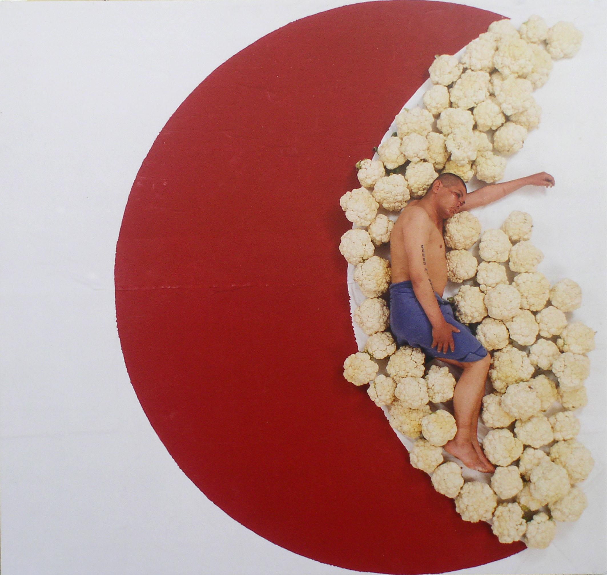 Półnagi mężczyzna leżący na tle czerwonego półksiężyca, otoczony kwiatami kalafiora
