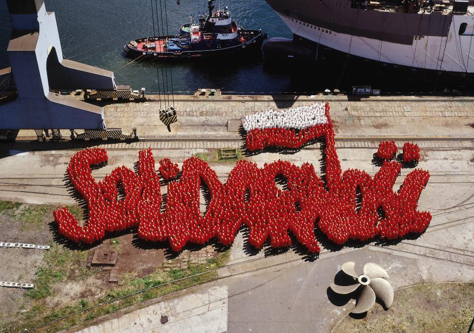 1 część dyptyku. Zdjęcie przedstawia kilka tysięcy żołnierzy, ubranych  w czerwone i białe bluzy, ustawionych  w taki sposób, że tworzą znak Solidarności. Dominuje czerwień, biel pojawia się w polskiej fladze. Stoją na betonowym nabrzeżu