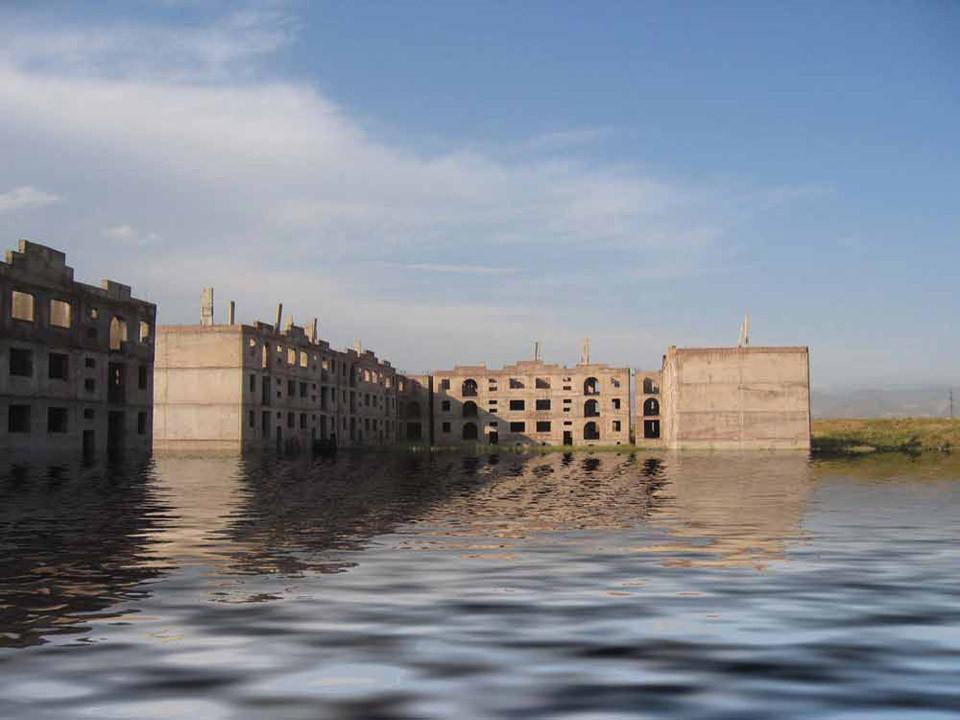 VahramAghasyan-9 Na zdjęciu  szkielet bloku  częściowo zatopionego  w wodzie. Nad nimi niebo, w tle budynki i góry.