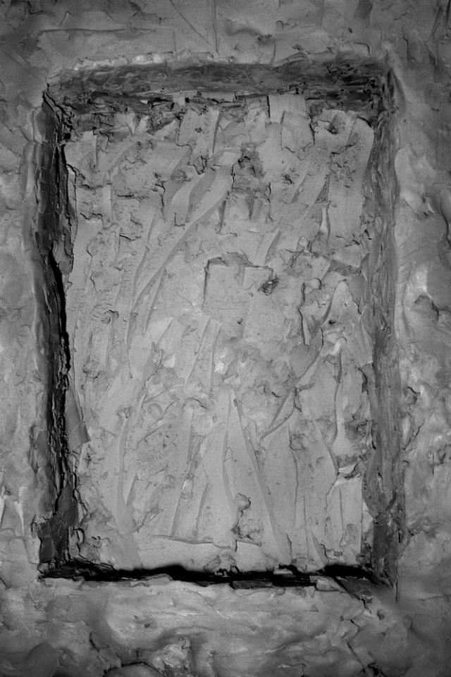 Na czarno-białej fotografii prostokątna dziura wykopana w glinie. Dziura niemal wypełnia kadr.