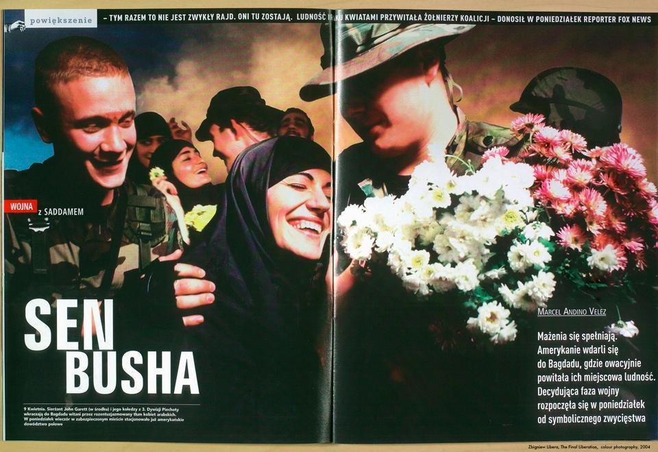 Fotografia przedstawia otwartą kolorową gazetę, tak rozłożoną, że wypełnia niemal cały kadr. Na otwartych stronach periodyku widnieje fotografia przedstawiająca irakijskie kobiety, witające z radością amerykańskich żołnierzy.