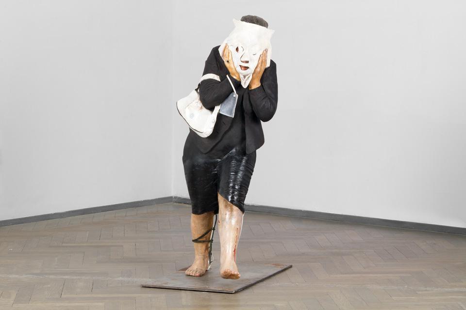 rzeźba kobiety nakrywającej twarz torbą z namalowaną twarzą
