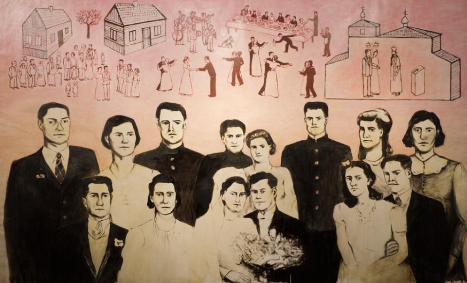 Obraz przedstawia postacie weselników oraz trzy budynki na płaskim różowo beżowym tle. Ludzie i budynki są malowane schematycznie, czarnymi liniami lub plamami.